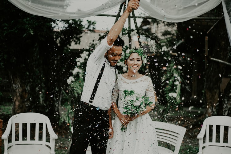 Biodegradable confetti popper being let off over newlyweds